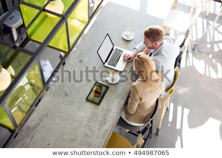 businessman and businesswoman using laptop in cafe stock photo © deandrobot