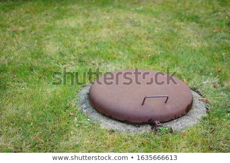 Stock photo: Water drain metal rusty hatch on green grass field. water drain drainpipe system