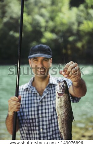 Fisher showing bait or lure at fishing rod Stock photo © Kzenon