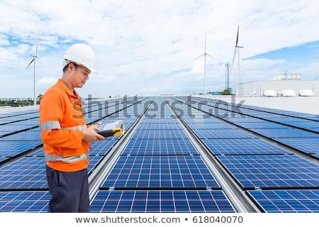 man checking solar panels and wind turbines stock photo © rastudio