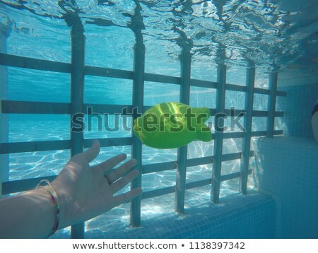 Child playing with generic rubber fish toy in swimming pool Stock photo © stevanovicigor