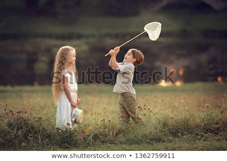 Young girl in field with butterfly net Stock photo © IS2