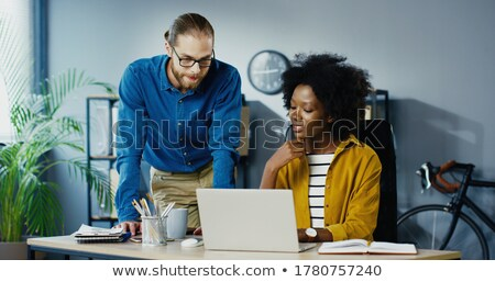 Boss looking at laptop with co-worker Stock photo © IS2