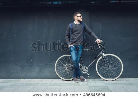 Young stylish guy next to bicycle stock photo © konradbak