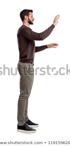happy young casual man pointing finger to side stock photo © feedough