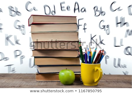 Stack of books by colored pencils in mug and apple on table against white background Stock photo © wavebreak_media
