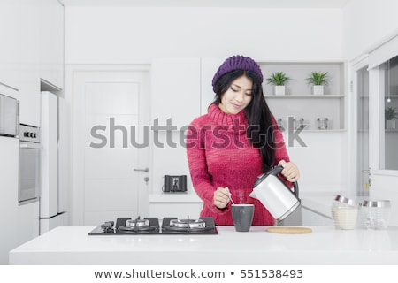 Woman pouring the water to the cup for drink in the kitchen Stock photo © dashapetrenko