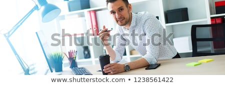 A young man is standing near a table in the office, holding a pencil and a glass of coffee. A young  Stock photo © Traimak