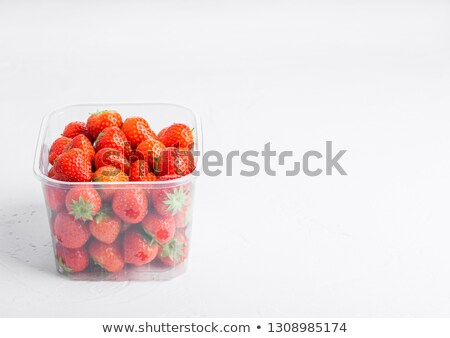 Plastic tray container of fresh organic healthy strawberries on stone kitchen table background. Tray Stock photo © DenisMArt