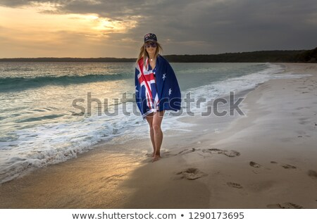 Woman draped in Australiabn Flag on a beach in early morning Stock photo © lovleah