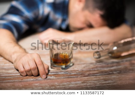 drunk man drinking alcohol at table at night stock photo © dolgachov