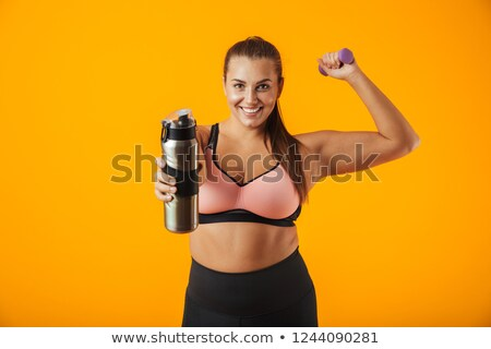 Portrait of european chubby woman in sportive bra holding thermo Stock photo © deandrobot