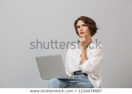 Gondolkodik fiatal nő ül zsámoly izolált szürke Stock fotó © deandrobot