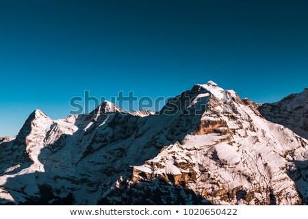Zwitserland bergen gedekt sneeuw wolken hemel Stockfoto © frimufilms