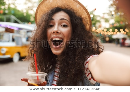 image of curly woman 20s wearing straw hat laughing while walki stock photo © deandrobot