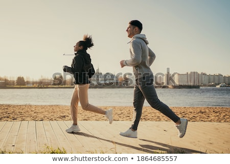 couple in sports clothes running along on beach Stock photo © dolgachov