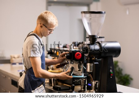 Young male barista in uniform with steel mug standing by modern coffee machine Stock photo © pressmaster