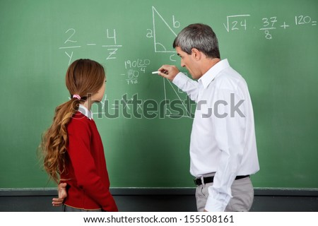 Side view of schoolgirl with math teacher writing on chalk board in classroom of elementary school Stock photo © wavebreak_media