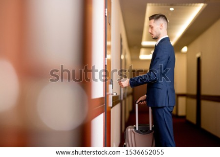 Young businessman holding plastic card by door while going to enter the room Stock photo © pressmaster