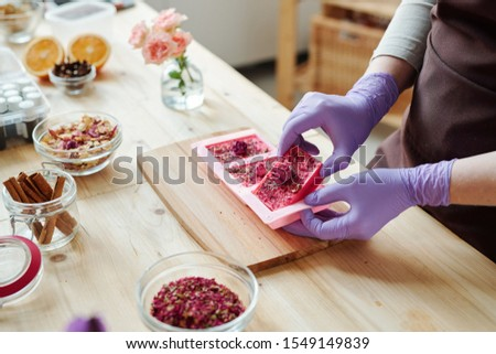 Hands of young woman taking out fresh handmade pink soap from silicone molds Stock photo © pressmaster
