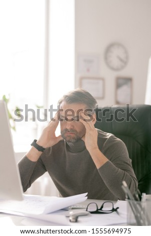 Mature tired businessman with his eyes closed trying to concentrate by workplace Stock photo © pressmaster