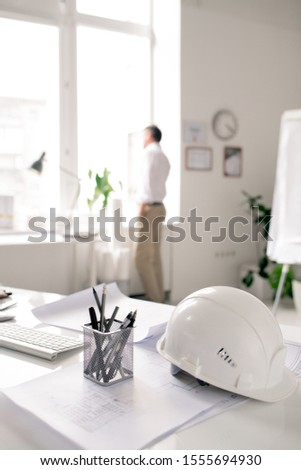 Workplace of modern architect with white hardhat, bunch of pencils and sketches Stock photo © pressmaster