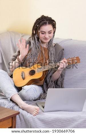 Contemporary young woman with dreadlocks enjoying music in headphones Stock photo © pressmaster