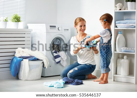 Happy mother loads clothes in washing machine, little girl helps, gives white linen from basket, do  Stock photo © vkstudio