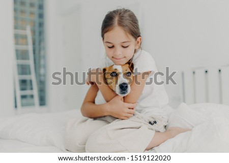 Indoor shot of happy small child embraces favourite pet, dressed in pyjamas, expresses love to her d Stock photo © vkstudio