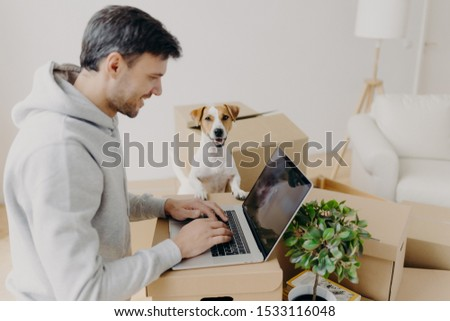 Sideways shot of man dressed in sweatshirt, purchases new furniture for apartment, surrounded with c Stock photo © vkstudio