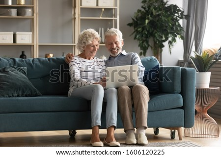 Cheerful husband and wife watch film online on laptop, rest on floor, relax and talk, their domestic Stock photo © vkstudio
