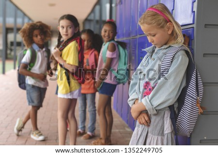 Side view of a sad schoolgirl standing in corridor while others school kids nteracting with each oth Stock photo © wavebreak_media