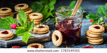 Banner of Cookie, biscuits filled with red raspberry jam on black table background. Stock photo © Illia