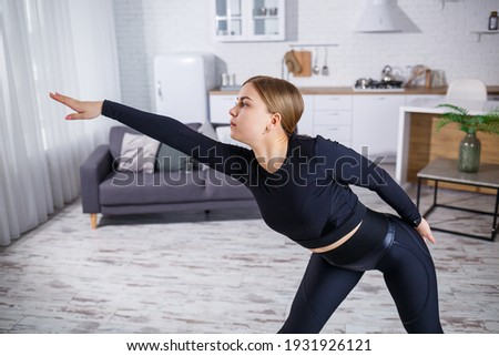 Young motivated fitness woman raises hands, does stretching exercises on floor, wears black sweatshi Stock photo © vkstudio