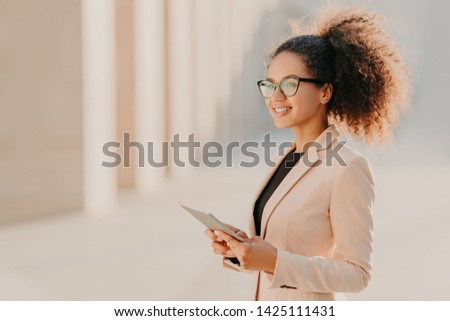 Profile shot of glad dark skinned woman with Afro hair, dressed elegantly holds tablet computer in h Stock photo © vkstudio