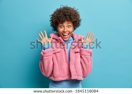 Photo of pleased surprised African American woman raises palms, keeps jaw dropped from wonder, focus Stock photo © vkstudio