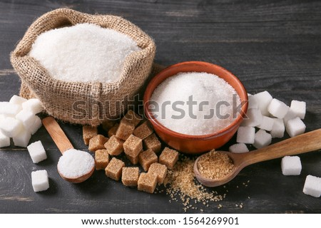 White bowl plates of natural brown sugar cubes and refined sugar on light table background. Stock photo © DenisMArt
