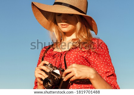 Photo of woman in red dress and straw hat holding retro photo ca Stock photo © deandrobot