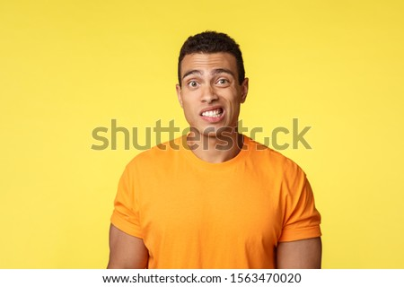 Yikes, awkward. Embarrassed young handsome man caught on lie, feel indesicive and slightly worried,  Stock photo © benzoix