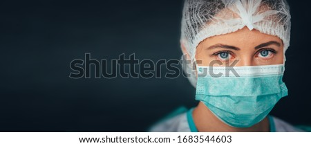 Female Doctor or Nurse Wearing Protective Face Mask and Surgical Stock photo © feverpitch