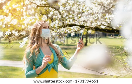 Stock photo: Woman enjoying the spring blossom despite the Coronavirus crisis