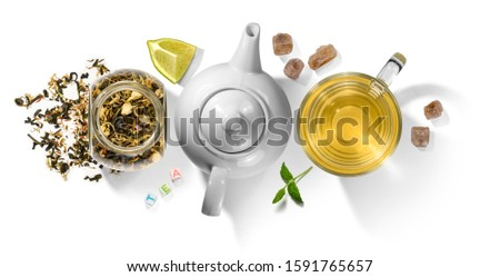 Green tea with natural aromatic additives and a teapot. Top view on white background Stock photo © butenkow