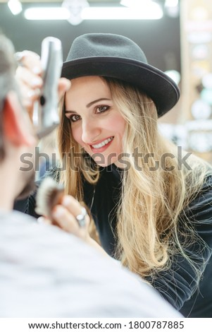 Woman barber cutting and trimming beard of client in her shop Stock photo © Kzenon