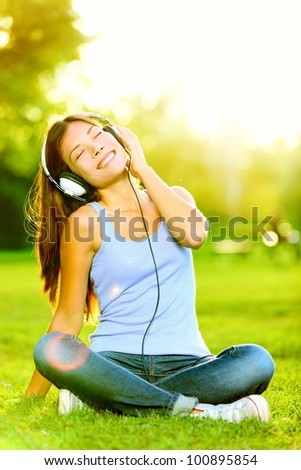 Student outside sitting on green grass and listening music via h Stock photo © HASLOO