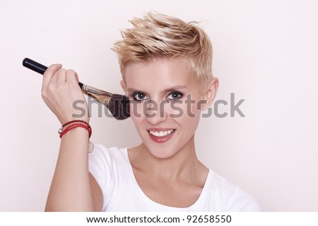 portrait of attractive young adult woman applying blusher agains stock photo © hasloo