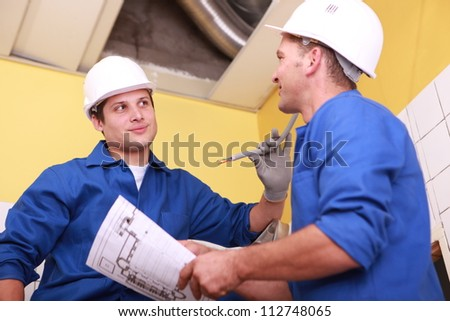 two skilled tradesman in blue jumpsuits working in housing under construction Stock photo © photography33