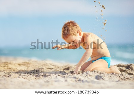 happy young boy is digging in the sand of the beach and constructing sand buildings Stock photo © meinzahn