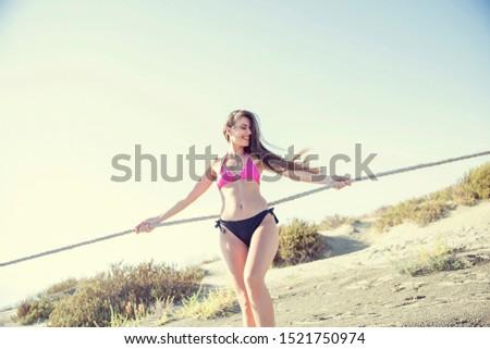 Young black woman at the beach, wearing a bikini. Leaning on railing. Blue sky. Stock photo © BrazilPhoto