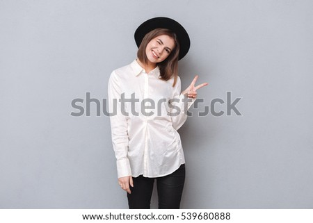 playful charming young woman winking and showing victory sign stock photo © deandrobot