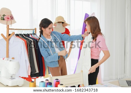 pretty woman fashion designer choosing models on photos in office stock photo © deandrobot